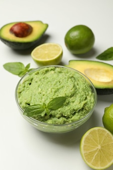 Bowl of guacamole, avocado, lime and basil on white background