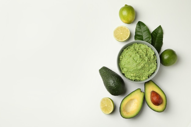 Bowl of guacamole, avocado and lime on white background, space for text