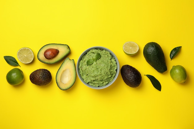 Bowl of guacamole, avocado and lime on yellow background, space for text