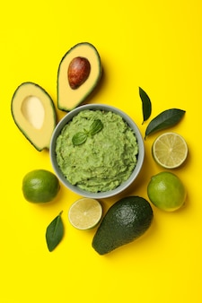 Bowl of guacamole, avocado and lime on yellow background, top view