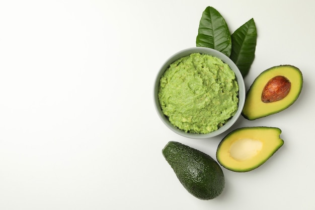 Bowl of guacamole and avocado on white background, space for text