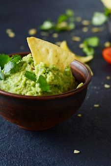 Bowl of guacamole dip with corn  nachos (chips) and ingredients on a blue wall, selective focus. mexican national dish.