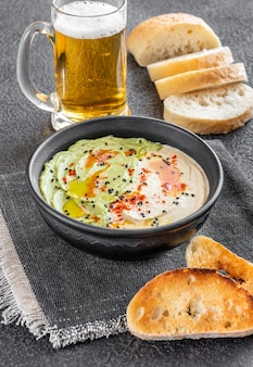 Bowl of guacamole and hummus with toasted bread