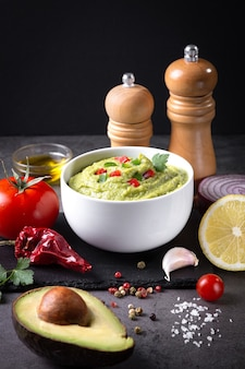Bowl of guacamole and ingredients on dark background  vertical format