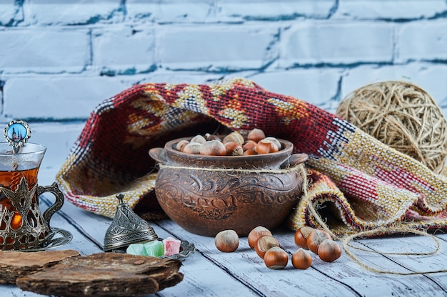 A bowl of hazelnuts on blue wooden table with carved rug and a cup of tea