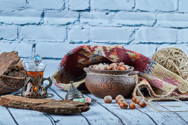A bowl of hazelnuts on blue wooden table with carved rug