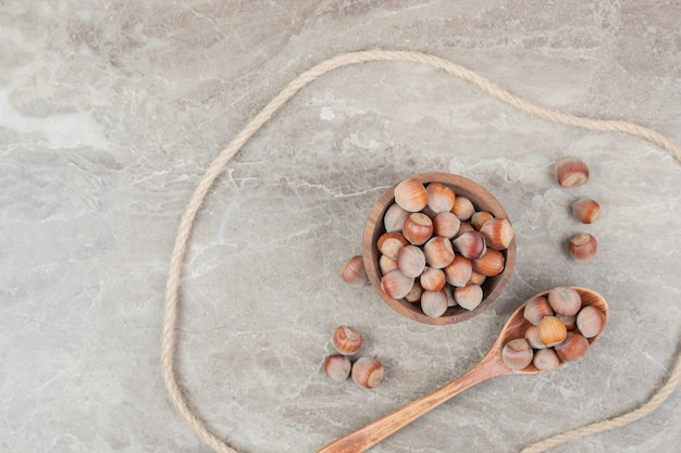 Ciotola di nocciole, cucchiaio e corda sul tavolo di marmo. foto di alta qualità