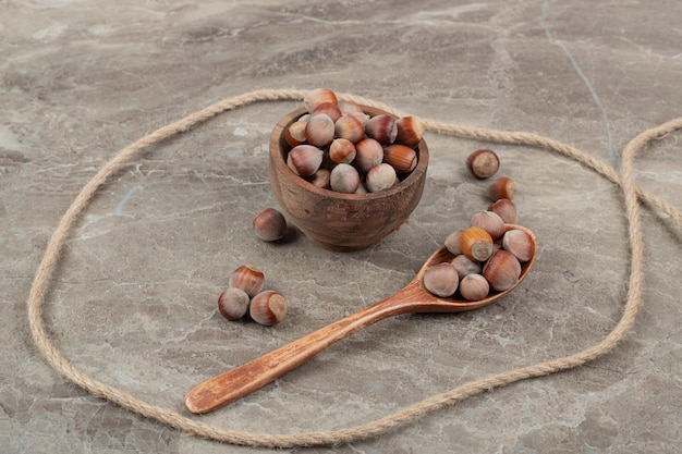 Bowl of hazelnuts, spoon and rope on marble table.