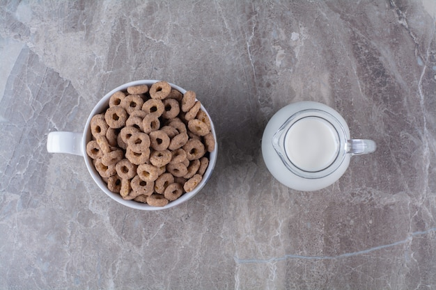A bowl of healthy chocolate cereal rings with a glass jar of milk.