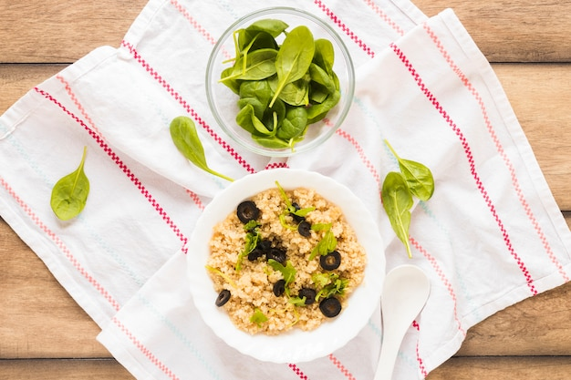 Bowl of healthy oats garnished with basil leaf and olive in bowl over cloth