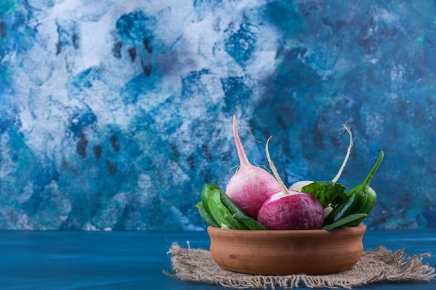 Bowl of healthy white and red radishes with greens on blue.