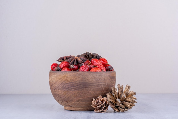 Bowl of hips and anise next to pine cones on white surface