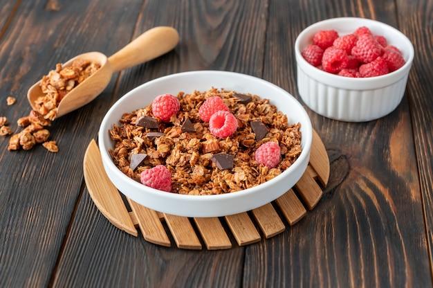 Bowl of homemade granola with fresh raspberries