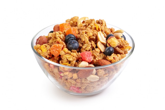 Bowl of homemade granola with fruit pieces isolated on white