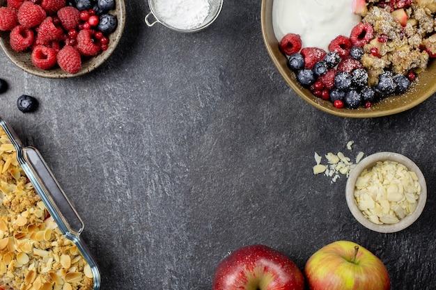 Bowl of homemade granola with yogurt and fresh berries on dark stone concrete.