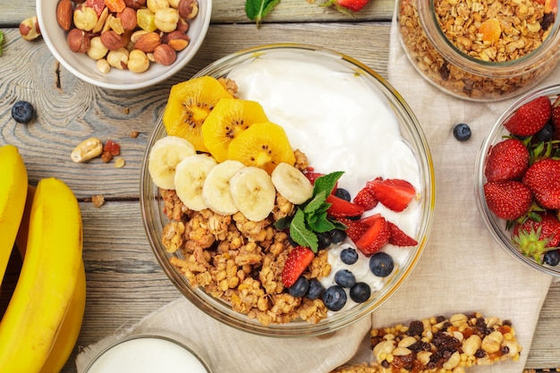 Bowl of homemade granola with yogurt and fresh berries on wood