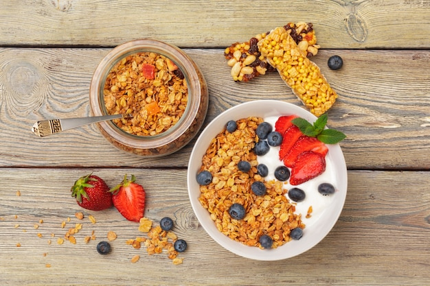 Bowl of homemade granola with yogurt and fresh berries on wooden surface
