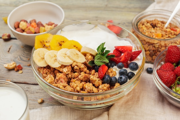 Bowl of homemade granola with yogurt and fresh berries on wooden table