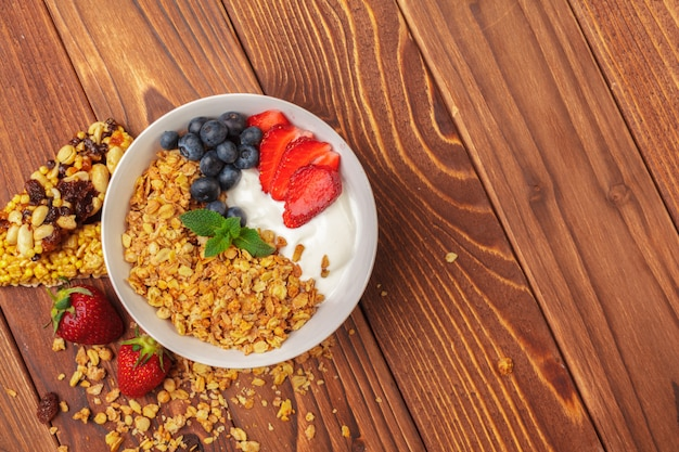 Bowl of homemade granola with yogurt and fresh berries on wooden