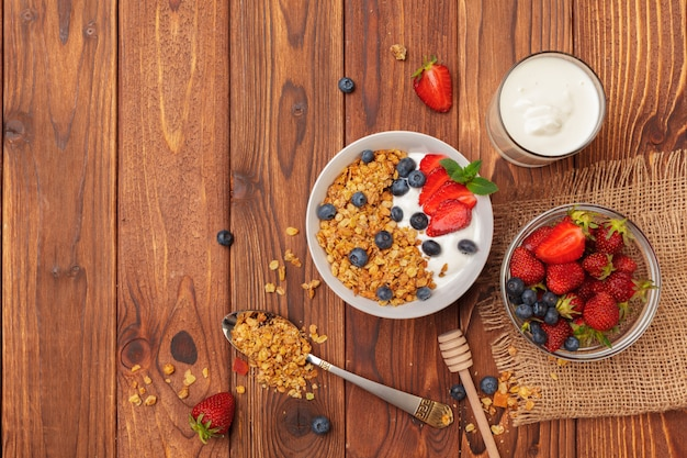 Bowl of homemade granola with yogurt and fresh berries on wooden