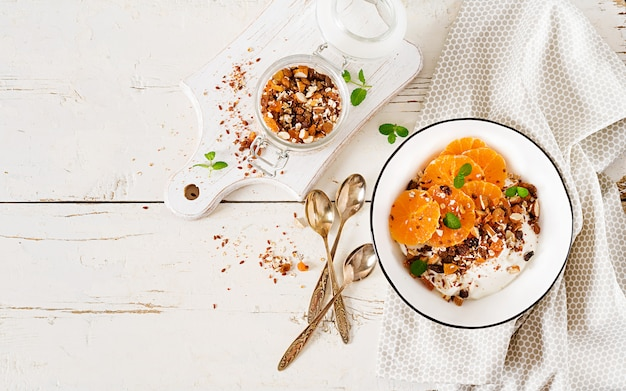 Bowl of homemade granola with yogurt and tangerine on white wooden table.