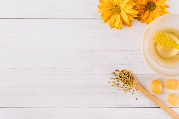 Bowl of honey; candies; bee pollen seeds and flowers on wooden background