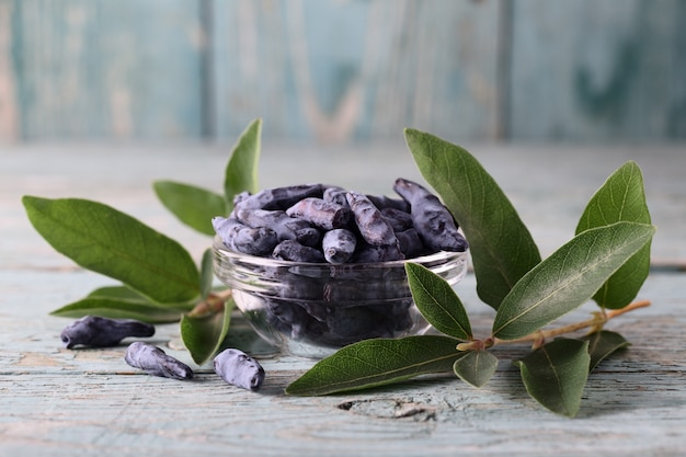 Bowl of honeysuckle berry on blue wooden background