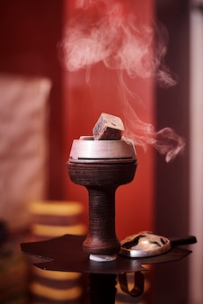 Bowl of hookah with hot coals in a cloud of smoke.