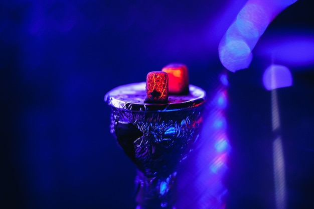 Bowl of the hookah with hot coals on the foil for smoking and relaxing