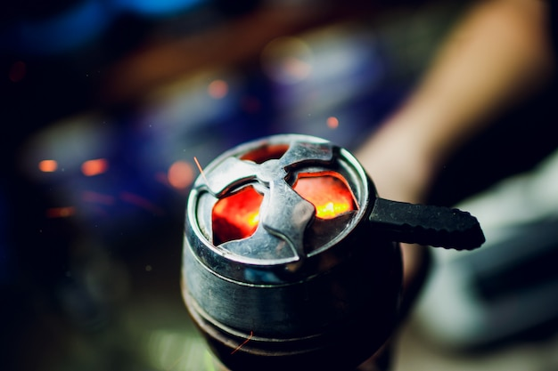 Bowl of the hookah with red hot coals in the hands of a hookah