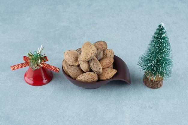 Ciotola di mandorle mondate e decorazioni natalizie su marmo.