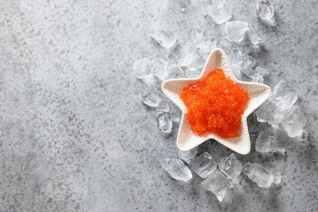 Чаша в форме звезды с красной икрой на льду на сером каменном столе. вид сверху. место для текста.