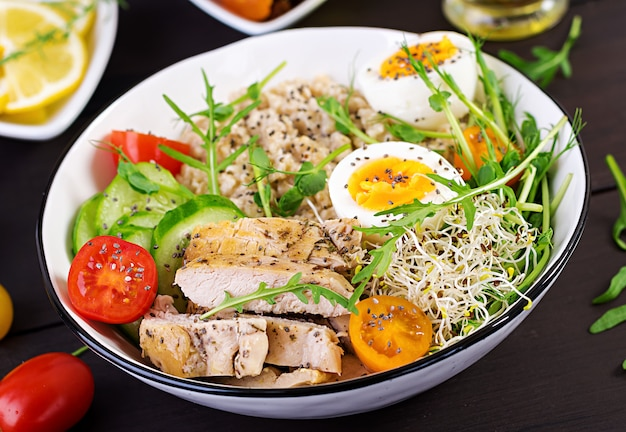 Bowl iwht oatmeal, chicken fillet, tomato, lettuce, microgreens and boiled egg