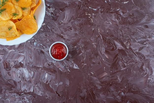 Una ciotola di ketchup e patate fritte in un piatto, sul tavolo di marmo.
