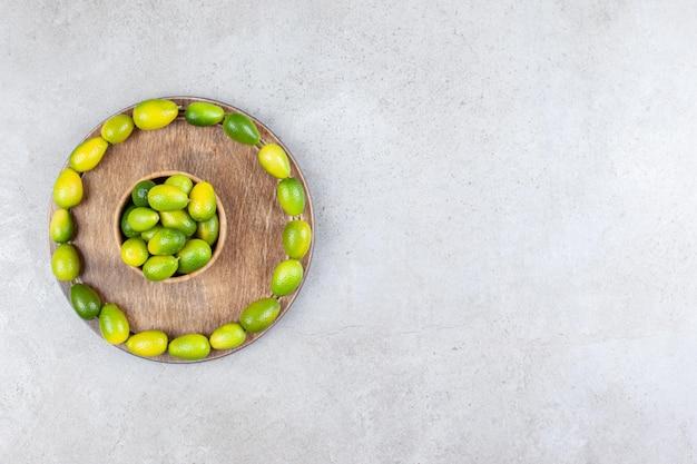 Ciotola di kumquat circondata da un cerchio di kumquat su una tavola di legno su fondo marmo.