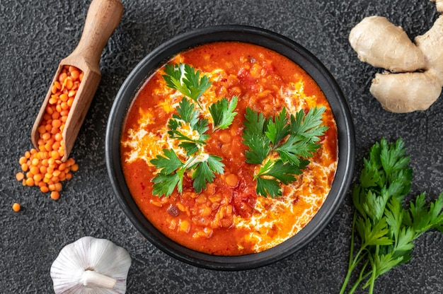 Bowl of lentil tomato and coconut soup flat lay
