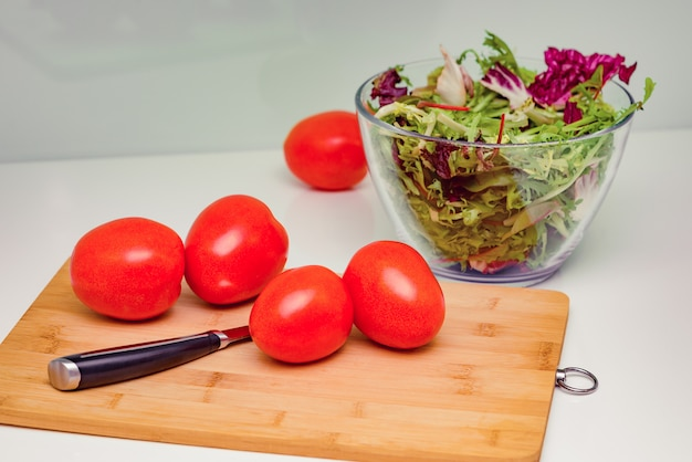 Bowl of lettuce leaves, ripe juicy tomatoes with knife on cutting board on white kitchen table.