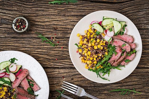 Обед с жареным бифштексом и киноа, кукурузой, огурцом, редисом и рукколой на деревянном столе