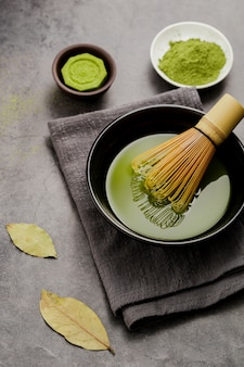 Bowl of matcha tea with bamboo whisk and cloth