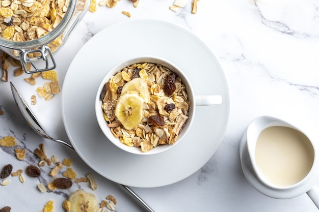 Bowl of milk with whole grains for breakfast muesli with dried fruits and dried fruits with copy space
