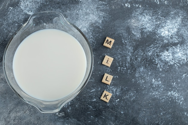 Bowl of milk and wooden letters spelled as milk.