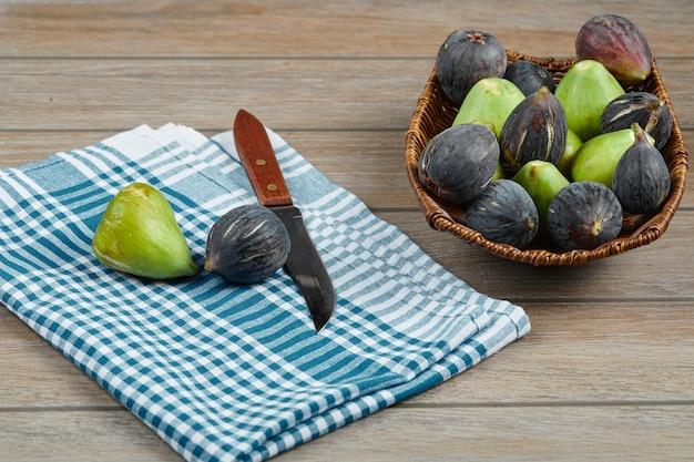 Una ciotola di fichi misti sul tavolo di legno con un coltello e una tovaglia.