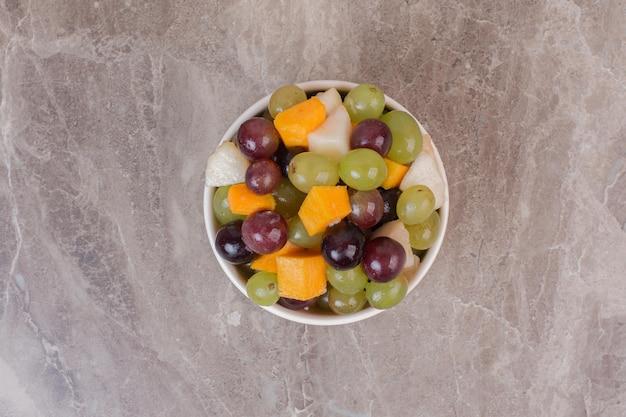 Ciotola di frutta mista su superficie di marmo.