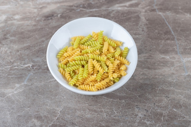 A bowl of mixed pasta , on the marble.
