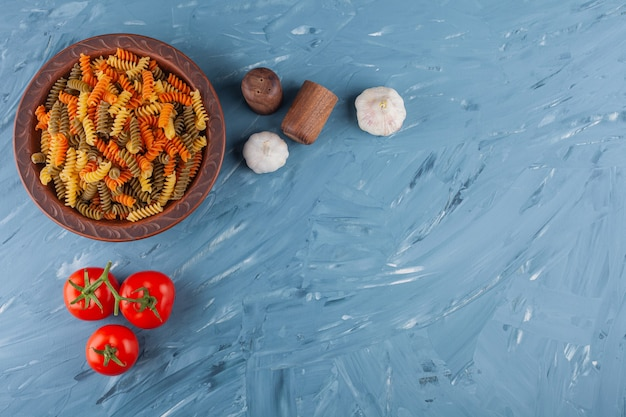 A bowl of multi colored raw spiral pasta with fresh red tomatoes and spices.