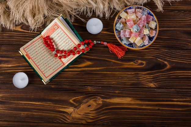 Bowl of multicolored lukum and red holy rosary beads and kuran with candles on wooden surface
