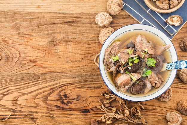 A bowl of mushroom lao duck soup on a cutting board