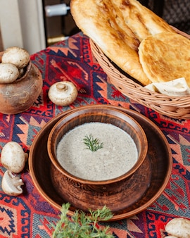 A bowl of mushroom soup garnished with dill