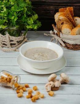 A bowl of mushroom soup served with bread stuffing, corriander on jar