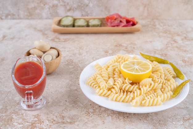 Bowl of mushrooms, appetizer tray of pickles, main course of macaroni and dressing of ketchup on marble surface.